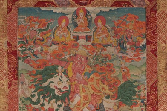 Tibet MSS 62, Box 24. Painting detail showing one large diety figure with three wide eyes at the center riding a lion. Five smaller figures float above him, the center three are robed in yellow and kneel on pillows. Flanking them to the right and left are two deity figures surrounded by deep orange flames.