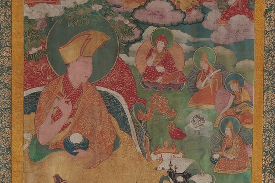 Tibet MSS 62, Box 41. Painting detail showing a large figure draped in yellow, red, and orange robes with a halo. To the right are four seated divine figures of a much smaller scale on a green ground.