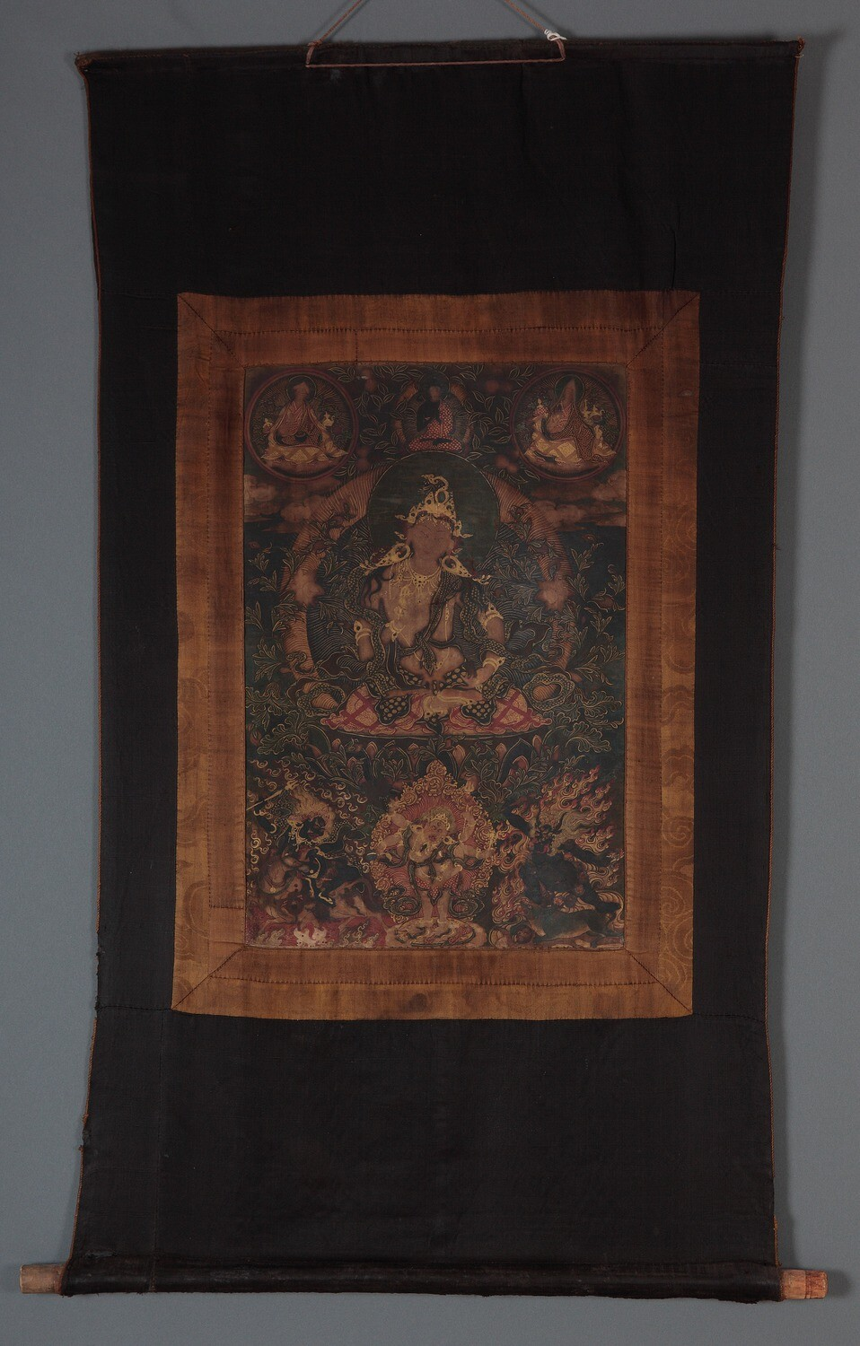 Tibet MSS 62, Box 72. Tanka painting mounted on dark colored fabric support. A figure is seated in the center of the painting, adorned with gold details. Six smaller figures, three above and three below, surround the central subject.