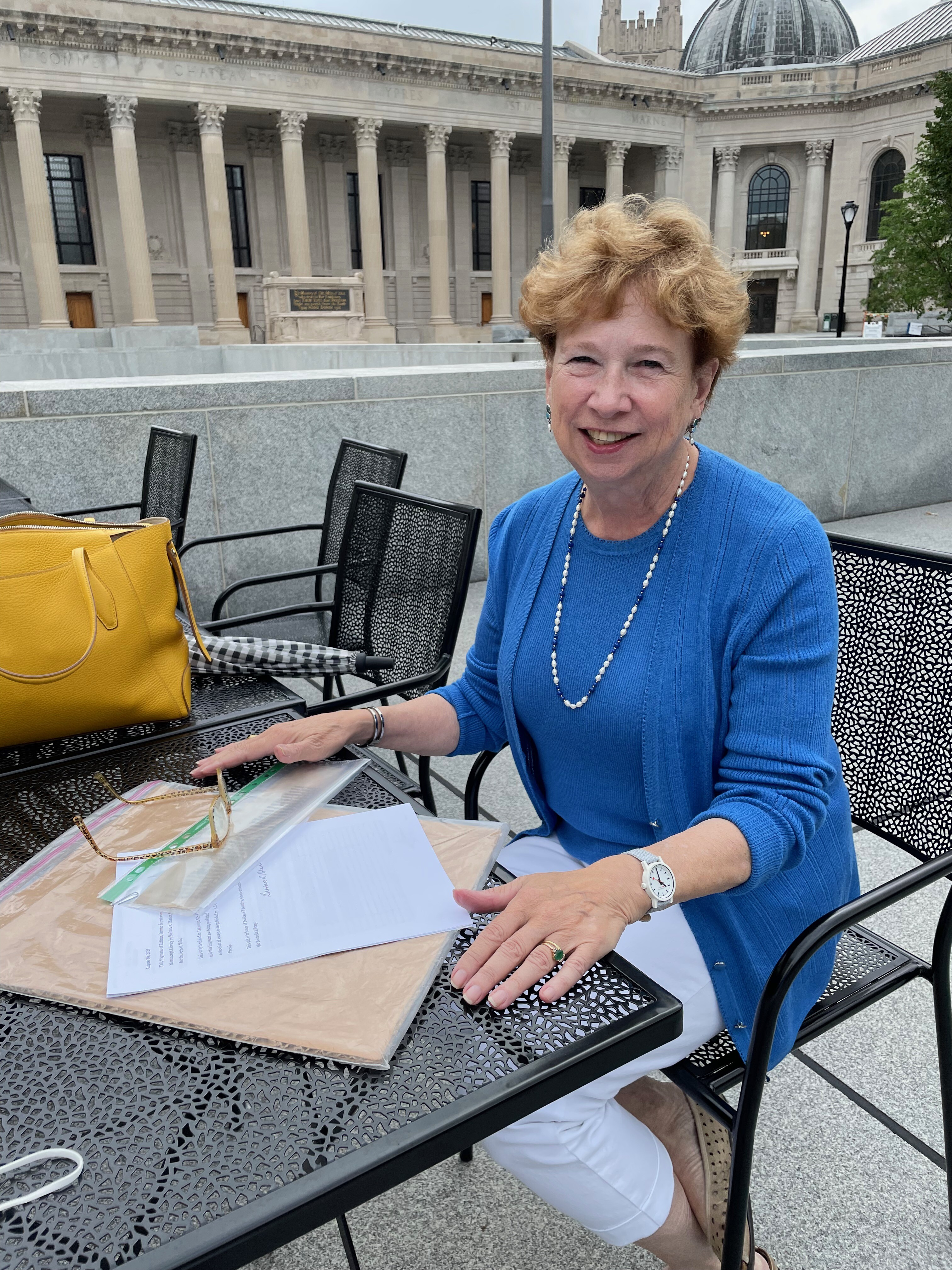 Barbara Shailor pictured seating in Beinecke Plaza with her donation in front of her.