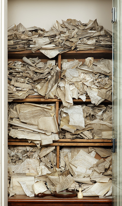 Picture of a closet with three wooden cases stuffed to overflowing with ancient charters. From the Grolier Club Library.