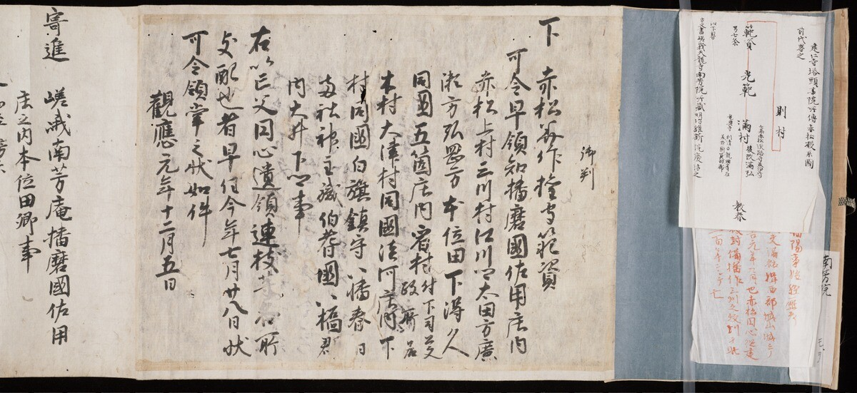 YAJ 2.2. Three pieces of light colored paper with Japanese script in black ink on a light blue support.