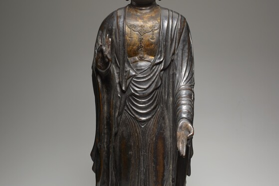 Bodhisattva, 14th Century. Yale University Art Gallery. A standing Bodhisattva figure dressed in clinging, flowing robes. The right hand is raised up to its chest and the left hand extends downward.